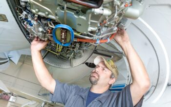 A Maintenance Technician for Priority Jet looking into an engine